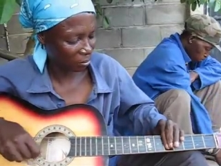 Beautiful african woman plays guitar in a slightly non-traditional manner